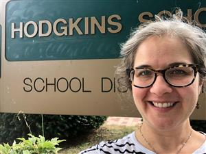 Dr. Crement in front of Hodgkins School sign.